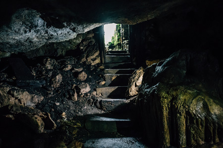 Exit from cave with stone steps, dark cave Stock Photo