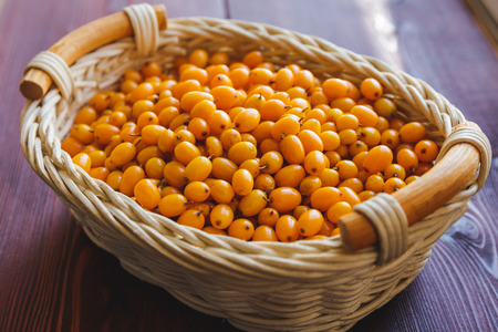 Freshly ripped sea-buckthorn in a wooden pot on a wooden background, selective focus Stock Photo