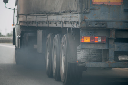 Air pollution from truck vehicle exhaust pipe on road, exhaust fumes concept Imagens