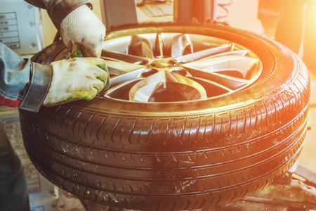 Mechanic worker makes computer wheel balancing in auto repair service, sun filter, selective focus, retro toned photo