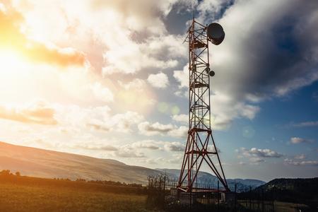 Tour de télécommunication avec antenne parabolique et mobile sur les montagnes au fond de ciel coucher de soleil, tonique