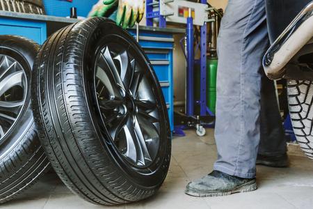 Mechanic changes car wheel in auto repair shop, toned