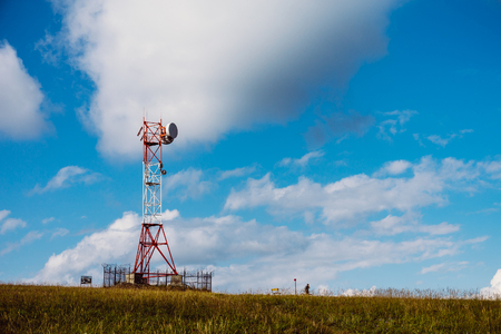 Communication tower antenna on mountain plateau against sky background in alpine terrain