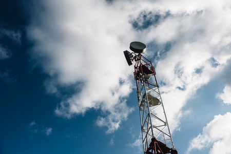 Antenna tower with the blue sky and clouds. Communication antenna, copy space, toned Stock Photo