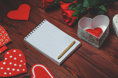 white sheet: Opened mock up notepad, toy hearts and red roses on wooden table. Romantic template. Valentines day concept. Toned image
