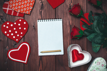 white sheet: Opened mock up notepad, toy hearts and red roses on wooden table. Romantic template. Valentines day concept. Toned image, top view. Stock Photo