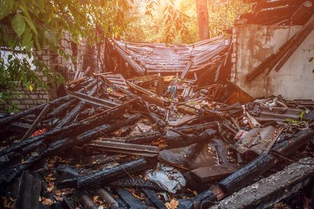 urban decay: Burned house, debris and ruins of destroyed building by fire, ash and coal, arson concept, toned