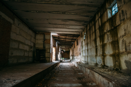Dark scary corridor in abandoned industrial ruined brick factory, creepy interior, perspective toned Stock Photo