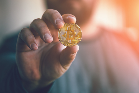 Cryptocurrency golden bitcoin coin. Man holding in hand symbol of crypto currency - electronic virtual money for web banking and international network payment, selective focus, toned