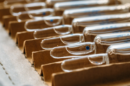 Glass vials or medicine ampoules. Injections of drugs, vaccine. Medical glass bottles with liquid, selective focus