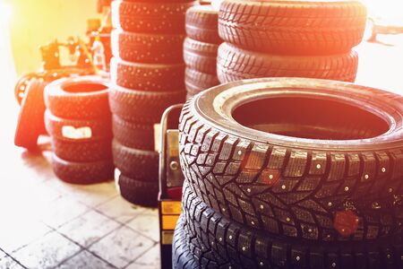 traction: New winter tires in stacks inside automotive garage service - changing wheels or tires, sunlight effect, toned Stock Photo