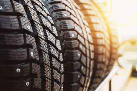 New winter tires for sale in store, selective focus, sunlight effect Foto de archivo