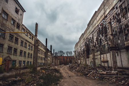 Apocalyptic concept, ruins of abandoned city, old broken factory or warehouse buildings, dark toned