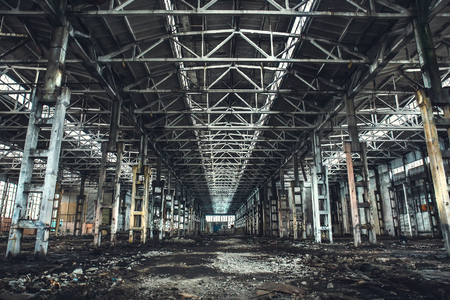 Large empty abandoned warehouse building or factory workshop, toned