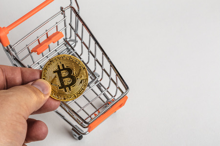 bitcoin network: Man hand puts golden bitcoin coin in little shopping cart, top view - symbol of crypto currency - electronic virtual money on white background with copy space
