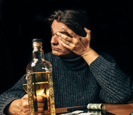 Alcohol and drugs abuse: portrait of young depressed man with problems, drinking whiskey and using cocaine, Narcotic and alcoholism addiction concept Stock Photo