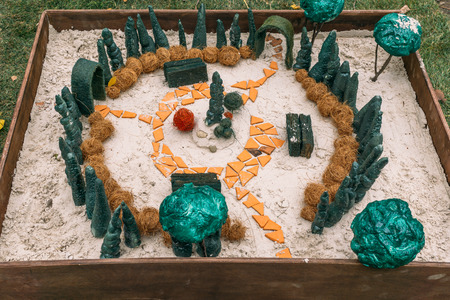 Miniature houses, toy landscape objects in sandbox. Anti-stress and soothing sand therapy. Landscape Layout