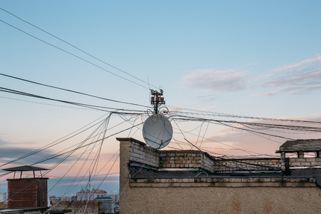 Satellite dish antenna and lots of cables roof top of modern house Banque d'images