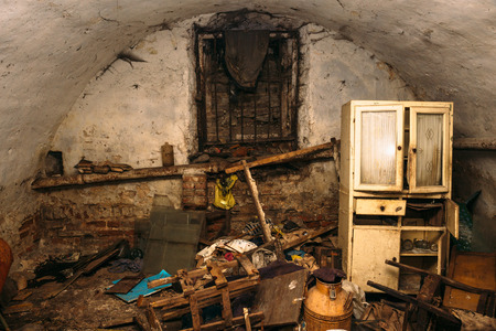 Old abandoned dirty shelter or basement of homeless people, old furniture and trash Stock Photo