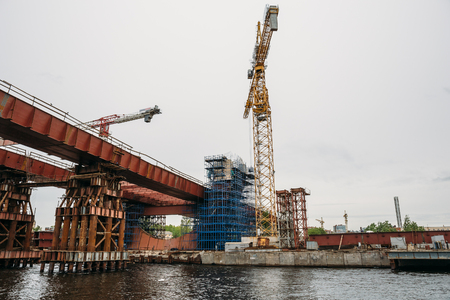 Construction of bridge with cranes and equipment over river in industrial zone, toned