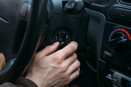 Closeup of male driver hand inserts key in ignition lock to start car Foto de archivo