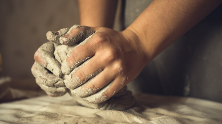 Female potter works with clay, craftsman hands close up, kneads and moistens the clay before work, toned Stock Photo