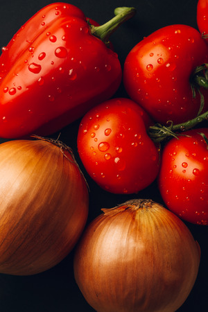 Fresh wet tomatoes in drops of water, golden onion, bell pepper on dark background, top view, vertical image Stock Photo
