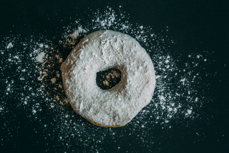 Delicious donut in white glaze on black background sprinkled with powdered sugar, top view, toned Stock Photo