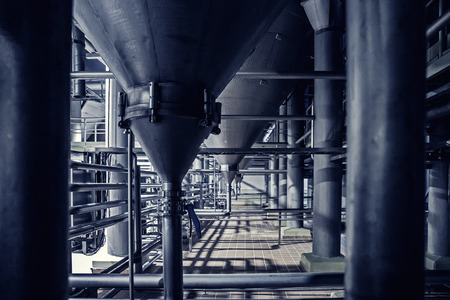 Steel pipes and filtration vats at brewery production beer factory, industrial background, toned