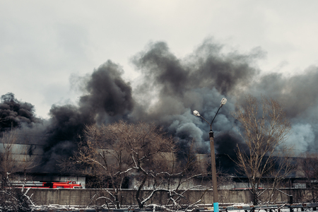 Fire in an industrial warehouse or Factory, rubber is burning, lots of smoke and flames