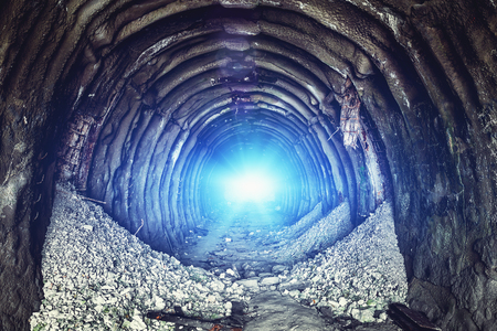 Mysterious blue light in the end of old round industrial tunnel or underground mine corridor. Escape and exit to freedom and hope concept, toned 스톡 콘텐츠