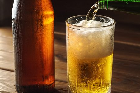 Pouring foaming beer into glass mug with drops near cold beer bootle on wooden table, craft brewing concept