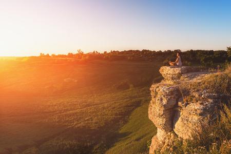 Bemannen Sie das Meditieren bei dem Sonnenuntergang, der auf Felsen am Gebirgshintergrund sitzt, getont