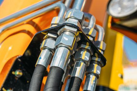 Sistema idraulico, tubi in acciaio e parti in gomma del meccanismo di sollevamento del moderno trattore o escavatore, macchine agricole Archivio Fotografico - 99354625