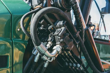 Hydraulisch systeem, stalen buizen en rubberen delen van hefmechanisme van moderne tractor of graafmachine, landbouwmachines, close-up