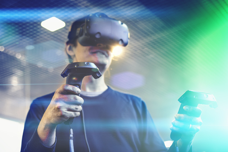 Young man use virtual reality  goggles or VR headset or helmet, play videogame with wireless controllers in hands, selective focus and light effects, future is now concept