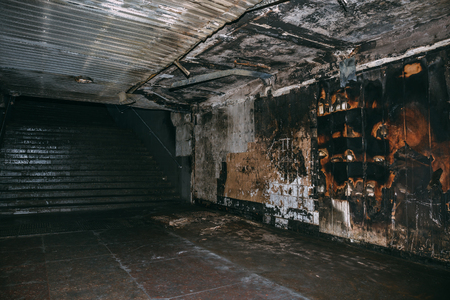 Burned underground pedestrian crossing after a fire or terrorist attack, walls in soot and smoke, dark toned Foto de archivo