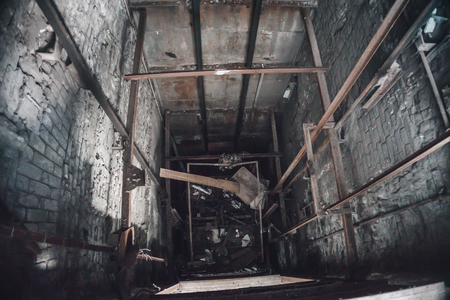 Broken Lift or elevator shaft or well in abandoned industrial ruined factory, toned Stock Photo