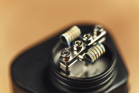 Coil of RDA atomizer for vaping or e-cigarette, vape macro footage, toned