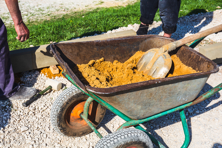 Wheelbarrow with sand and workers hands on construction site, close up
