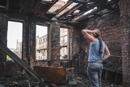Sad man holds his head by hand and cry in burnt out house after disaster. Loss and despair concept, consequences of fire Фото со стока