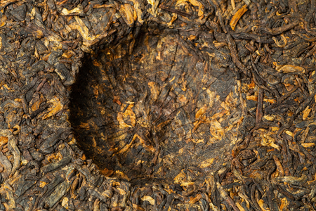 Cake of old Chinese Black tea Shu pu-erh or puer, traditional asian drink, macro shot, top view