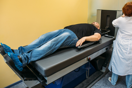 Male patient on treatment of intervertebral discs and spinal hernia, stretching spine on special medical machine tool. Modern physical therapy, health care concept Stock fotó
