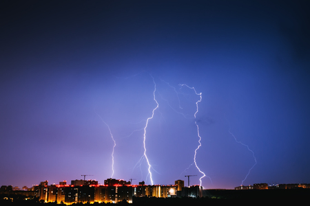 Thunderstorms vivid blue sky and lightnings above night city, toned
