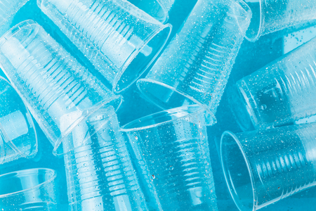 Empty transparent disposable plastic glasses in drops of water on bright blue background,  top view