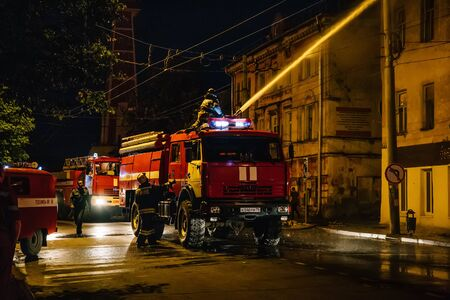Rybinsk, Russia -31 July 2018 : Firefighters with fire hose and fire engines or trucks are fighting fire in residential building at night. Huge smoke, hot flame in burning house