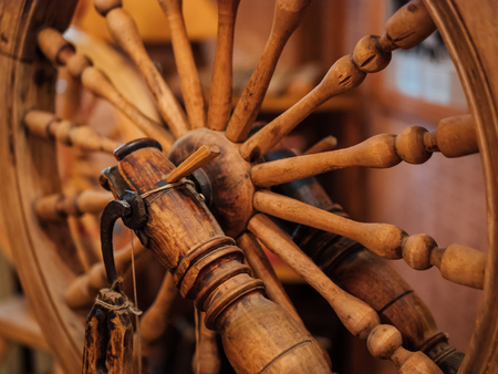 Old antique wooden spinning wheel, close up, selective focus