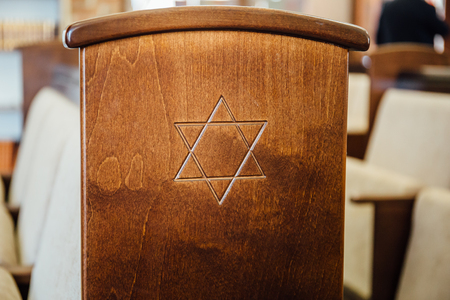 Star of David, Jewish symbol on wooden bench or chair in synagogue, close up Stock Photo