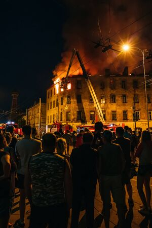 Rybinsk, Russia -31 July 2018 : Night fire in apartment building, firefighters struggle with flame, people stand around. Fire disaster and accident tragedy