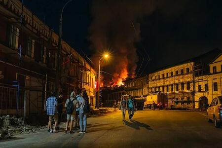 Rybinsk, Russia -31 July 2018 : Large night fire, burning modern building, smoke clouds, flames, people on the street watching the fire Redactioneel